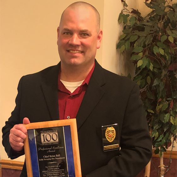 Chief Brian Ball holding the award plaque.