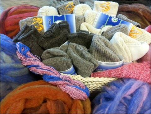 a variety of wool socks, hats, and yarn in a basket